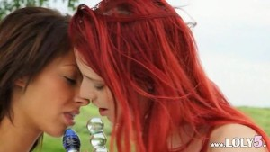 Redhead and brunette women in the grass