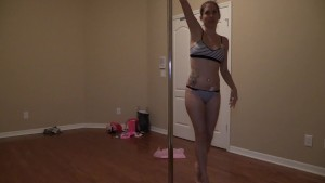 Amateur girl poledancing while