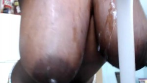 Curvy ebony playing with her huge tits in the kitchen...