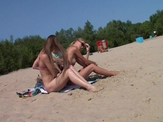 Nudist girls have fun with each other at the beachclick to edit