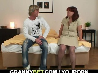 Redhead granny in stockings rides his rod