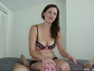 A cute brunette milf gives a younger guy a POV handjob on his bed.