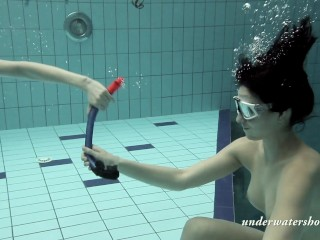 Girls swimming underwater together with taking eachother