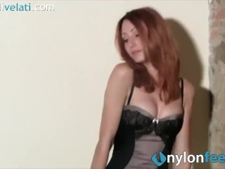 Redhead in pantyhose takes off her heels and shows foot soles