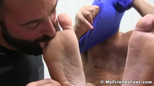 Hunky bearded dude West observes while his feet are licked