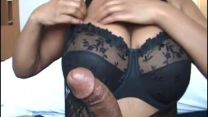 Thick and busty black lady wanks a cock