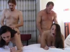 Two beautiful ladies swap partners in a swingers orgy