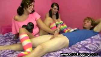 Two horny teens stroke their friends hard cock as they tease him