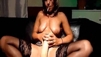 Mature slut fucks a giant dildo whilst smoking