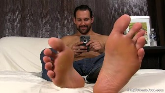 Jet shows off his clean feet on the bed